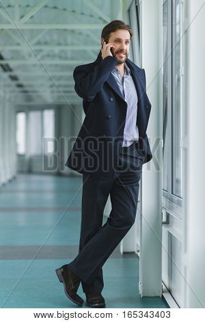 elegant businessman with cell phone dressed coat