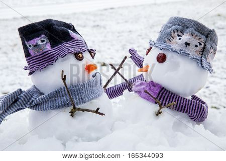 Two cute snowmen dressed for winter in scarfs and hats embracing each other as long lost friends. Winter scene with snow.