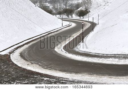 Mountain winding road going down among the snow in winter.