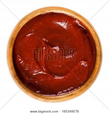 Tomato ketchup in wooden bowl. Also called catsup or ketsup, is a red table sauce made from tomatoes, often used as a condiment. Isolated macro food photo close up from above on white background.