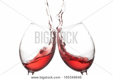 Two red wine glasses and splashing action on white background. Cheer celebration concept photo. Macro view photo.