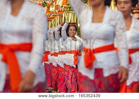 DENPASAR BALI ISLAND INDONESIA - JUNE 11 2016: Group of beautiful women in traditional Balinese costumes carry on head religious offering for hindu ceremony on parade at art and culture festival.