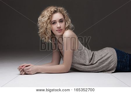 studio portrait of blond woman with curly hair lying on white background