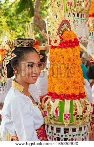 DENPASAR BALI ISLAND INDONESIA - JUNE 11 2016: Beautiful woman in traditional costume. Group of Balinese people with religious offering for hindu ceremony on parade at art and culture festival.