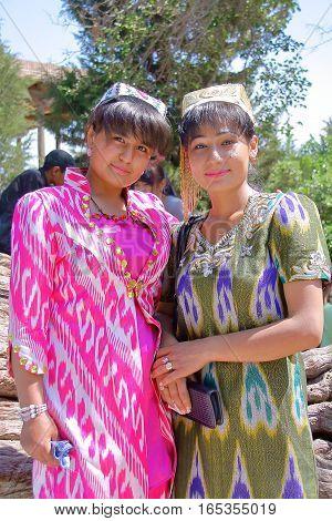 BUKHARA, UZBEKISTAN - MAY 11, 2011: Two young Uzbek women traditionally dressed posing inside the Bakhautdin Naqshband mausoleum near Bukhara