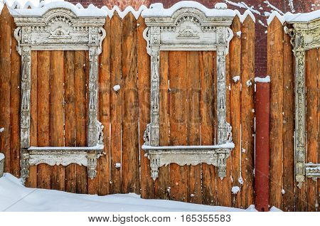 Antique wooden window frame in the Russian style as decorative element on a red fence made of boards covered with snow, like vintage background