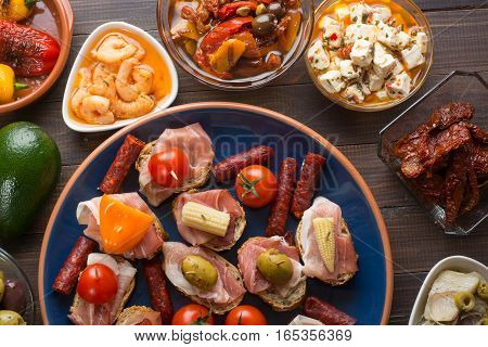Variety of Mediterranean snacks on old wooden table. Tapas or antipasti. Top view