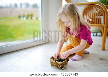 Cute little girl playing with colored Easter eggs at home on Easter day. Celebrating Easter at spring. Painting quail eggs.