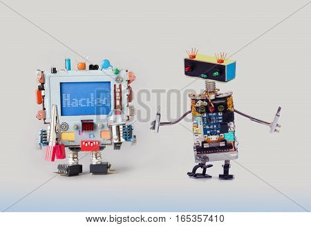 Cyber crime concept. IT specialist robot serviceman with screwdrivers looking at colorful computer. Alert warning message Hacked blue display. Gray gradient background
