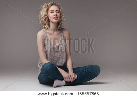 fashion studio portrait of blond woman with curly hair sitting on light grey background