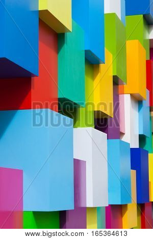 Abstract colorful architectural objects. Violet blue red green white yellow blocks with different colors variation. Vertical photo. Geometric shapes