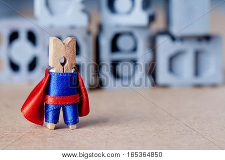 Cute toy super hero character. Clothespin blue suit and red cape. Gray building blocks background