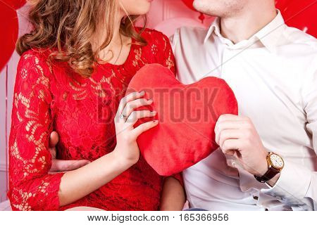 Couple holding red heart shaped pillow and loking each other
