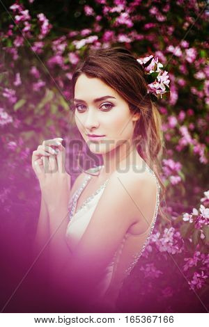 Portrait of young beautiful woman posing among blooming apple trees. Professional make-up and hairstyle. Perfect skin. Fashion photo. Natural beauty. Springtime.