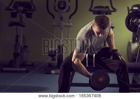 Young muscular built athlete working out in a gym sitting on a weightlifting machine and lifting a dumbbells