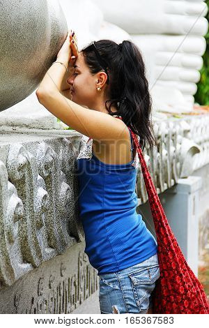 Girl with black hair at the recumbent Buddha statue makes a wish. Picture taken in Thailand.