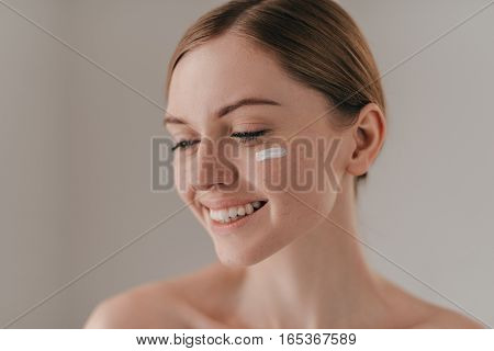 Pampering cream. Young woman looking away and smiling while standing against grey background