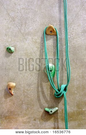 Green rope with a knot hanging in a climbing wall.