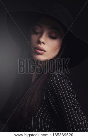 Beautiful woman wearing retro hat and black stripwd shirt. fashion studio shoot.