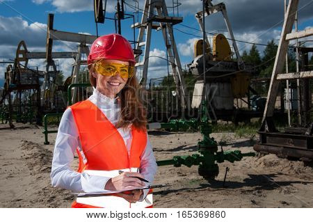 Woman engineer in yellow glasses on the oil field wearing red helmet and work clothes. Industrial site background.