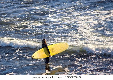 Photo of a long-board surfer preparing to enter the sea