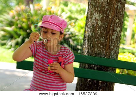 Pretty little girl blowing soap bubbles in a park