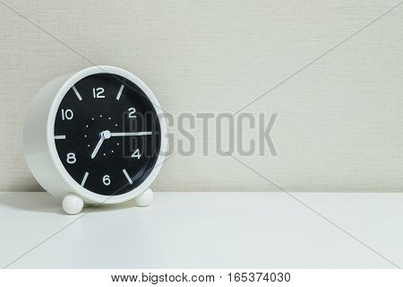 Closeup black and white alarm clock for decorate show a quarter past seven or 7:15 a.m.on white wood desk and cream wallpaper textured background with copy space