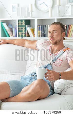 young hipster man at home, relaxing, drinking coffee