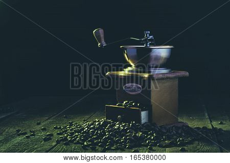 Handle coffee mill with beans on dark background. Yellow light