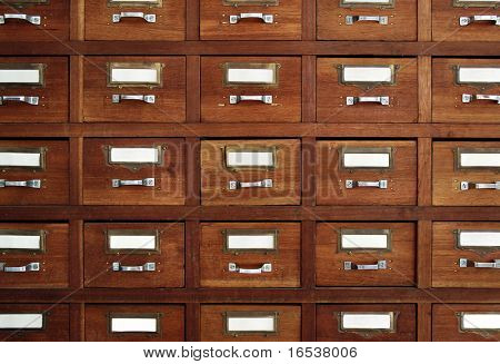 Rows of little drawers with white empty tags in an old furniture module