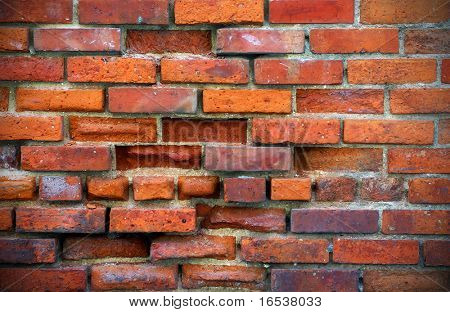 Photo of an old damaged brick wall with gaps and holes.
