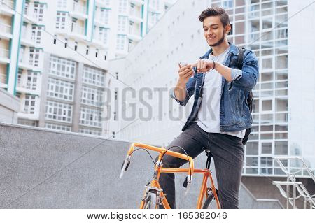 Man riding a bicycle outside. Happy guy stopped to take nice picture of the interesting building or he is just scrolling on his mobile phone. Urban background