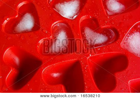 Closeup of red ice tray with heart-shape ice and water drops