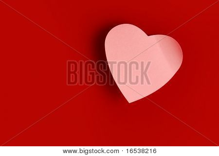 Background of one heart-shaped pink post it over red