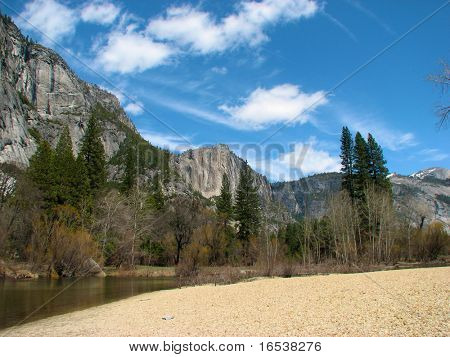 Yosemite valley on a beautiful day with blue sky framed by pine trees clouds and a river beach