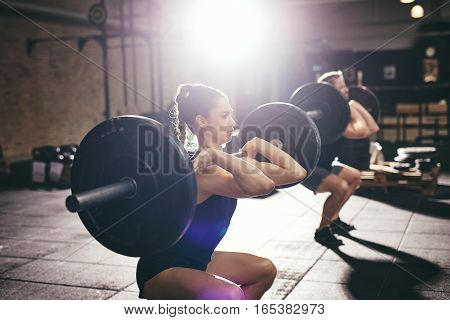 Man And Woman Lifting Barbells At Gym