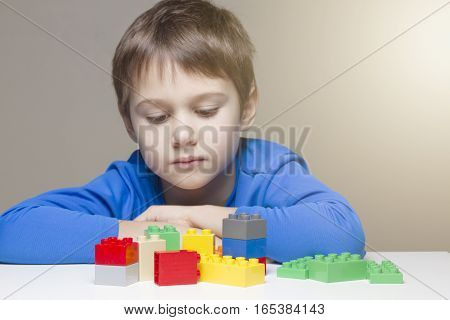 Sad child sittings and looking at colourful plastic construction toy blocks at the table. Children, toys, leisure concept