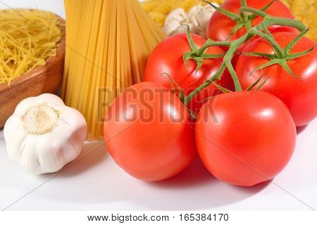 Ripe Tomatoes Branch, Uncooked Italian Pasta Spaghetti And Garlic On A White