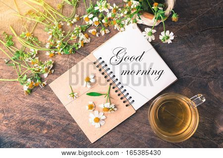 Good morning text on notebook with white flower and basket of flower and cup of tea on vintage wooden table View from above with warm light.