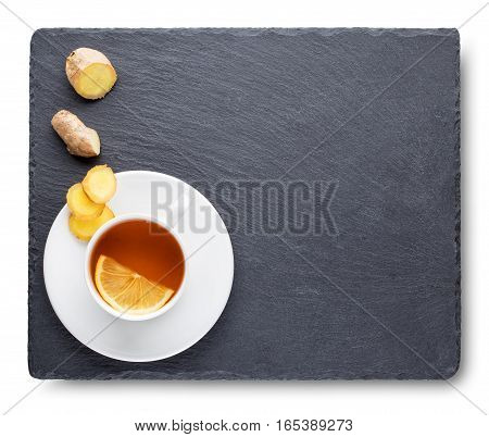 Tea with lemon and ginger root on slate blackboard isolated on white background