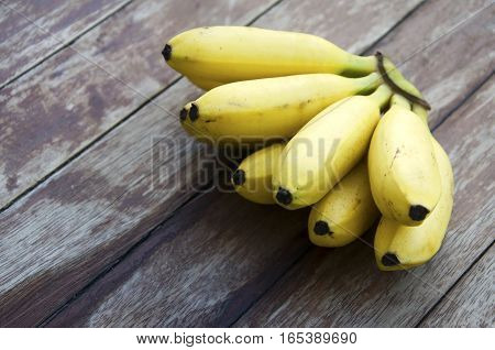 Banana yellow with a wooden floor in the background.