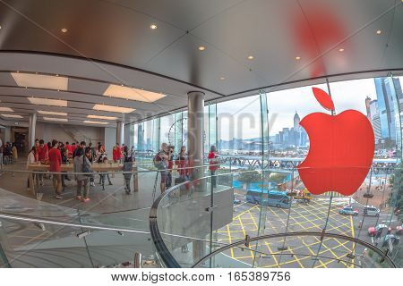 Hong Kong, China - December 4, 2016: Red Apple sign and customers looking the new technological products and shop clerks in red. Apple store, IFC Mall, with Observation Ferris Wheel on background.