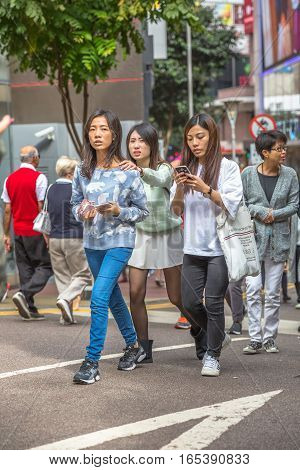 Hong Kong, China - December 6, 2016: asian young women walking talking at their mobile phone in Jardine's Crescent street market of Causaway Bay, on background luxury shops of famous brends.