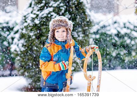 Little boy enjoying sleigh ride. Child sledding. Toddler kid riding a sledge. Children play outdoors. Kids sled in snowy park in winter. Outdoor fun for family Christmas vacation. Fir trees and snow.
