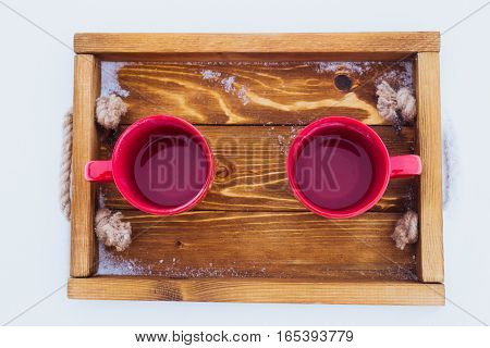 Overhead shot of two red cups with tea on a wooden tray in snow. Romantic winter picnic couple going to drink hot tea. Lifestyle winter walk time outdoors. Snowflakes hoarfrost on a tray