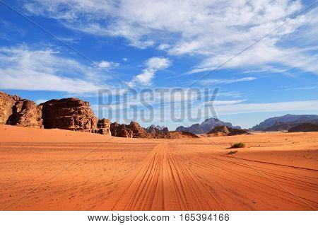 Dirt road in the Wadi Rum (Moon Valley) desert landscape at sunset time Jordan