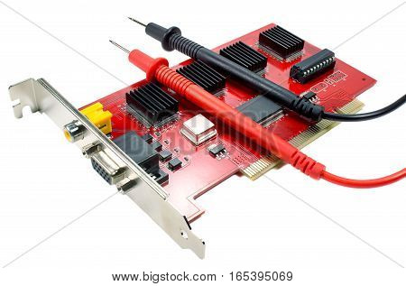 DVR motherboard with the probes of the multimeter on a white background