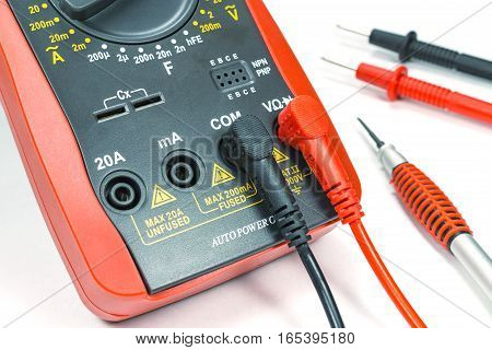 Digital multimeter with probes and screwdriver on white background