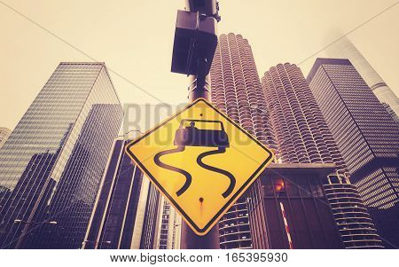 Color toned slippery when wet road sign with curvy tracks Chicago skyscrapers in distance conceptual picture.