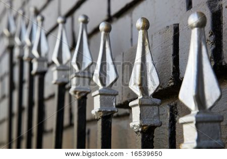 Black Sliver tipped Gate steel fence against painted bricks